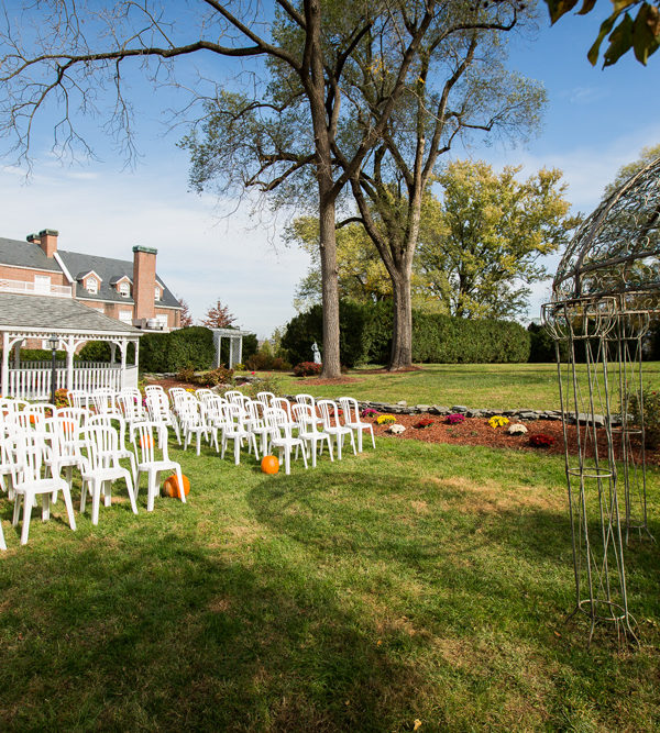 wedding ceremony set up with white chairs and pumpkins