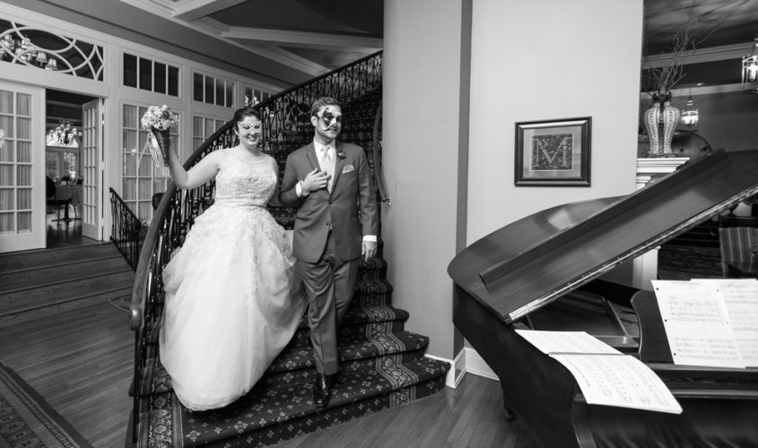 bride and groom walking down mimslyn inn staircase in masquerade masks