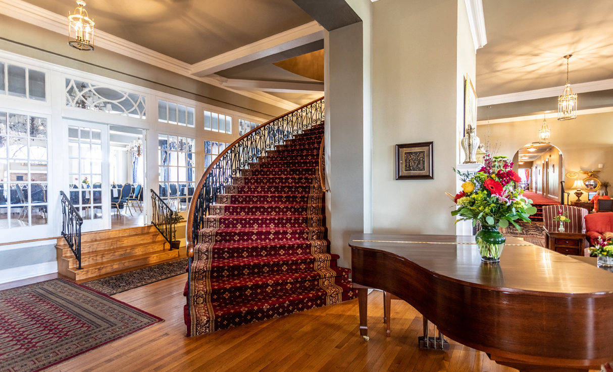 Lobby of the Mimslyn Inn, showing a piano and a spiral staircase