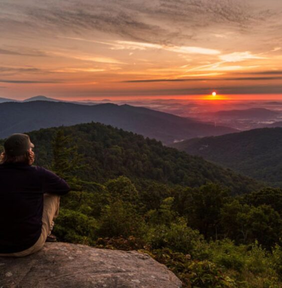 Hiker sitting on a rock looking over mountains at sunset.